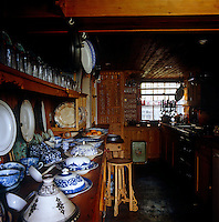 A selection of blue and white china is laid out on the worksurface in the basement kitchen