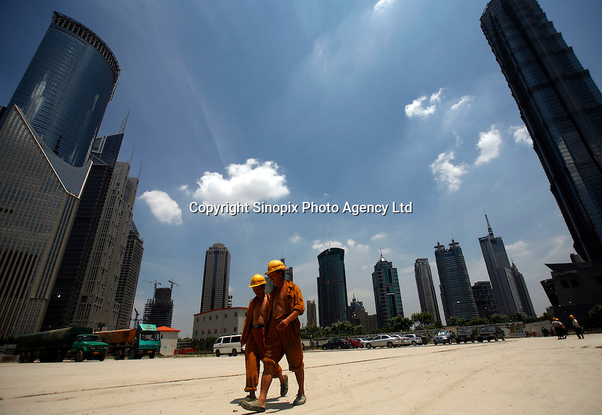 Workers walk through  a construction site in Shanghai, China..