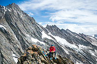 A trail runner resting and eating on the summit of the Strahlegghorn, with the Lauteraarhorn in the background. Grindelwald, Switzerland.