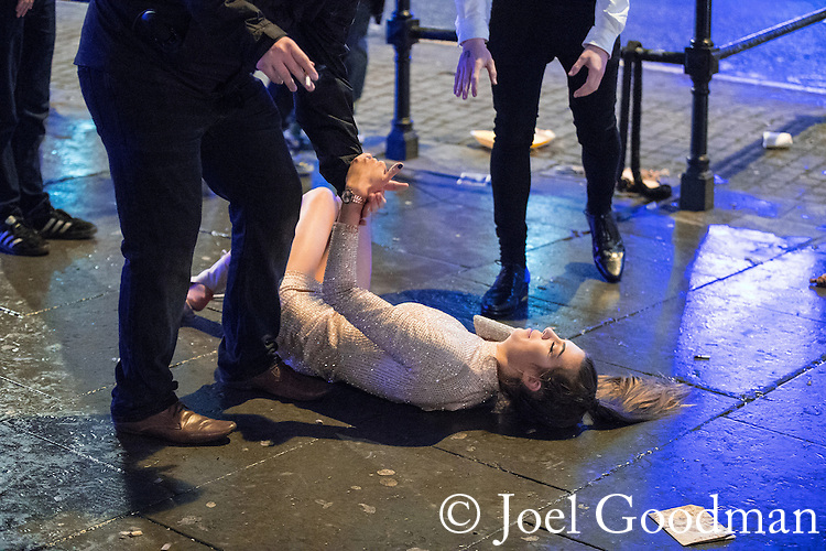 "© Joel Goodman - 07973 332324 . 17/12/2016 . Manchester , UK . A woman slips on the pavement and several men step forward to help her up . Revellers out in Manchester City Centre overnight during "" Mad Friday "" , named for being one of the busiest nights of the year for the emergency services in the UK . Photo credit : Joel Goodman"