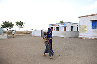 A woman carries her child away from a rural village 'Anganwadi' (nutrition clinic), in western Madhya Pradesh, India. The clinic is open for one morning a week, to enable local mothers to access nutrition advice and supplementary food, to improve the health of their children.
