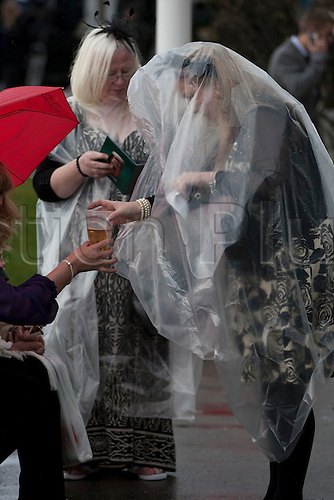 13.04.2012 Aintree, England. The Grand National Festival Ladies Day. A woman wearing a protective plastic rain cover is handed a pint of beer by a friend during a break between the races.