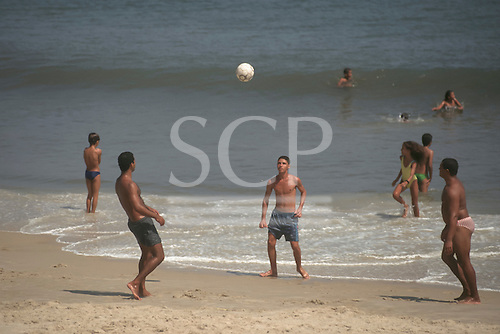 Rio de Janeiro, Brazil. Group of young men playing beach football with swimmers in the sea behind.