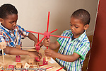 Brothers ages 6 and 3 playing with wood stick and cub construction toy horizontal