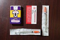 Clockwise: A Narcan (Naloxone) injector which blocks and reverses the effects of heroin and other opioids; a North Carolina syringe access card; and sterile syringes. The card exempts carriers from arrest and prosecution for possession of needles, other drug paraphernalia, and trace amounts of heroin. All are available at the Twin City Harm Reduction Collective, a needle exchange for addicts, at Green Street Church in Winston-Salem, NC.