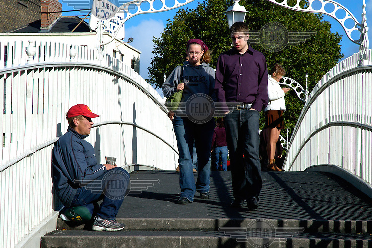 People passing a homeless man begging on the Ha'penny Bridge, the symbol of the city of Dublin.