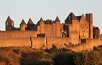 Citadel of Carcassonne at sunset, 13th century, Carcassonne, Aude, France. The two outer walls of the concentric fortified city are defended by towers and barbicans, and a draw bridge across a moat leads to the keep of the castle. Carcassonne was a stronghold of Occitan Cathars during the Albigensian Crusades but was captured by Simon de Montfort in 1209. He added extra fortifications and Carcassonne became a citadel on the French border with Aragon. The fortress was restored in 1853 by Eugene Viollet-le-Duc. Today it is a UNESCO World Heritage site. Picture by Manuel Cohen.