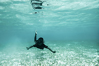 A Bajau child swims through a field of seagrass near his village of Pulo Papan in Sulawesi, Indonesia.
