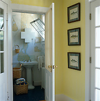 View through an open door into a small cloakroom with a wash basin