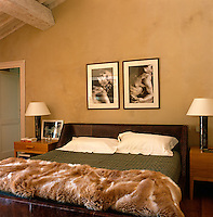 The contemporary bed is upholstered in leather and the room is simply if sparsely furnished and adorned with photographs by Fiorenzo Niccoli