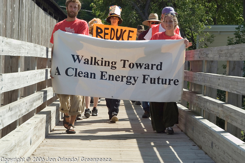 Rebecca Sobel (right) and Will Bates of Project Hotseat, lead a march on the outskirts of Burlington on the second day of a five day walk across Vermont to raise awareness on Global Warming.