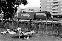 Switzerland. Chiasso. An old woman lays down and sleeps under the sun on a chaise longue in the swimmingpool's garden. A truck passes by on the highway. © 1998 Didier Ruef