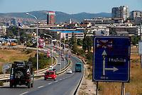 Pristina / Kosovo - 8/2011.Veduta della capitale del Kosovo. Sulla destra un cartello stradale in cui è stata cancellata la direzione per Belgrado e scritto il nome del poliziotto albanese ucciso il 25 luglio 2011 durante gli scontri nella zona di confine controllata dai serbi a nord di Mitrovica..Foto Livio Senigalliesi
