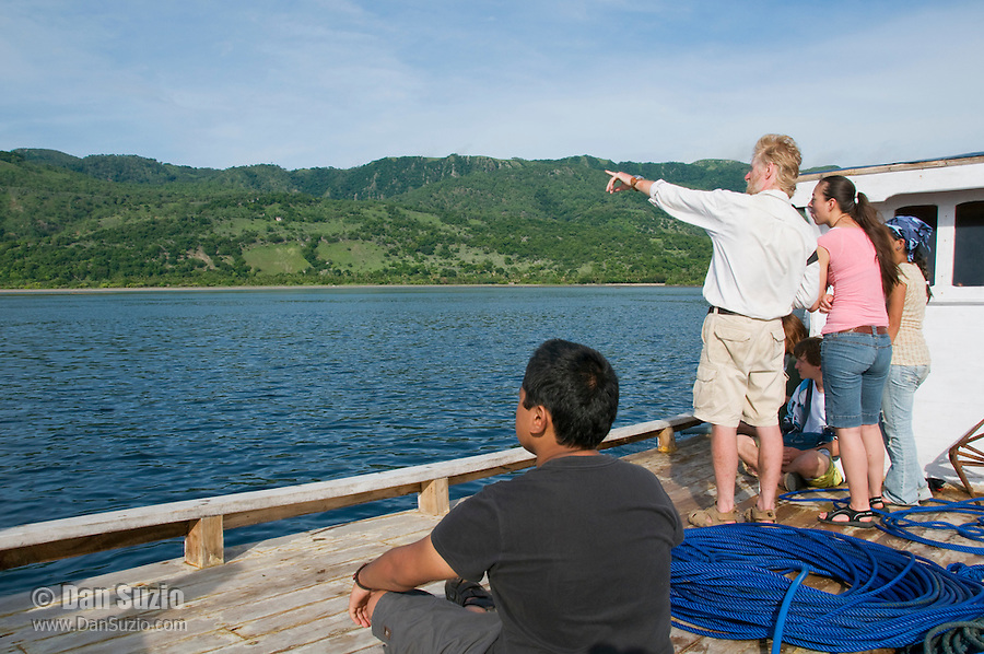 British herpetologist Mark O'Shea stands with American students Jester Ceballos, Caitlin Sanchez, and Marianna Tucci on the deck of a small boat leaving the dock at Beloi, Atauro Island, bound for Dili, Timor-Leste (East Timor)