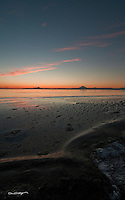 A tide change on Cook Inlet occurs with the sun setting behind Mount Redoubt and Mount Iliamna on the beach at Kenai, Alaska.