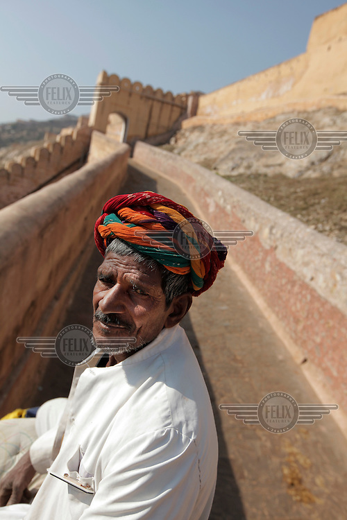 An mahout, or  elephant driver,  taking tourists to Amber Fort. It was the ancient citadel of the ruling Kachhawa clan of Amber, before the capital was shifted to present day Jaipur. Amber Fort is known for its unique artistic style, blending both Hindu and Muslim (Mughal) elements.The fort borders the Maota Lake, and is a major tourist attraction in Rajasthan.