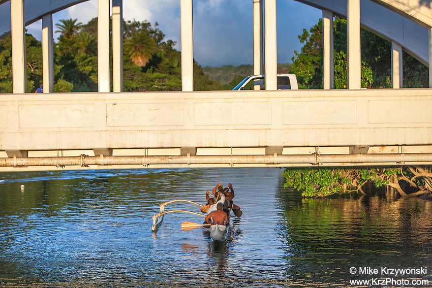 Local Hawaiian men paddling a canoe on Anahulu Stream under the bridge in Haleiwa, Oahu, Hawaii