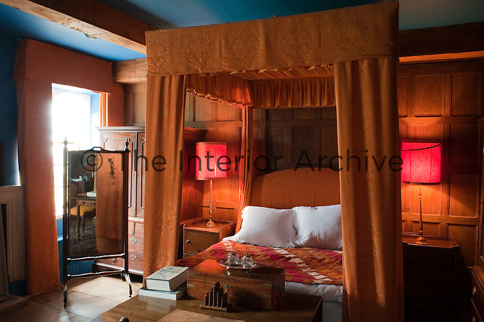 A four-poster bed takes centre stage in The Orange and Blue Room