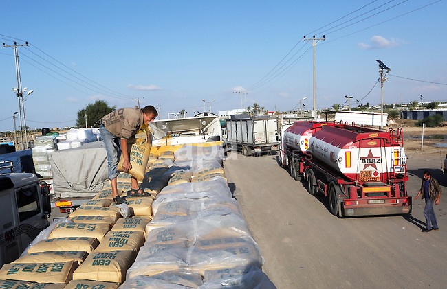 A Palestinian worker adjusts bags of cement loaded on a truck that entered the Gaza Strip from Israel through the Kerem Shalom crossing in Rafah in the southern Gaza Strip on November 5, 2014. UN peace envoy Robert Serry announced on November 4 that the temporary reconstruction mechanism for the war-torn Palestinian territory had begun operations, under the auspices of the newly formed Palestinian unity government, noting the urgency in providing cement and other materials to tens of thousands of damaged homes in Gaza ahead of winter. Photo by Abed Rahim Khatib