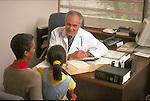 male doctor explaining diagnosis to woman and child in doctor's office