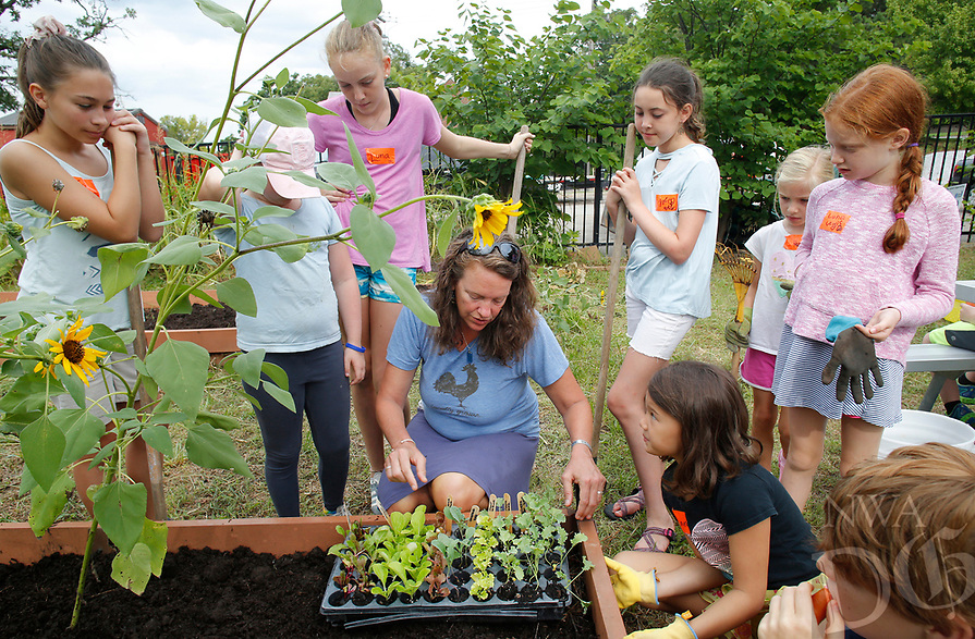 NWA Democrat-Gazette/DAVID GOTTSCHALK Melissa Terry (center), school garden coordinator, describes the method for planting Wednesday, August 8, 2018, to students participating in the Washington Elementary School Garden Club Back to School Summer Camp at the school in Fayetteville. The campers are prepping and planting a fall garden at the school and participating in recreational and educational activities in the surrounding neighborhood.