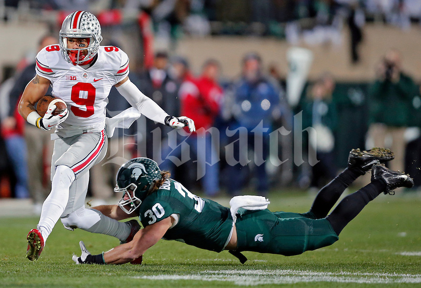 Ohio State Buckeyes wide receiver Devin Smith (9) gets past Michigan State Spartans linebacker Riley Bullough (30) after a catch during the 1st quarter at Spartan Stadium in East Lansing, Michigan on November 8, 2014.  (Dispatch photo by Kyle Robertson)