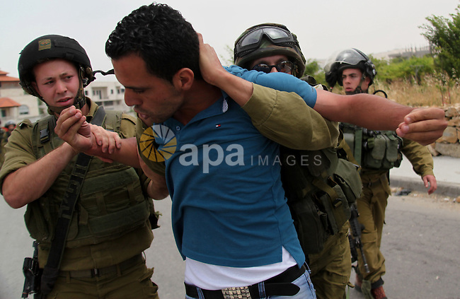 Israeli soldiers detain a photographer during a protest in support of Palestinian prisoners on hunger strike in Israeli jails at the al-Aroub Palestinian refugee camp, just north the West Bank town of Hebron on May 31, 2014. Photo by Mamoun Wazwaz
