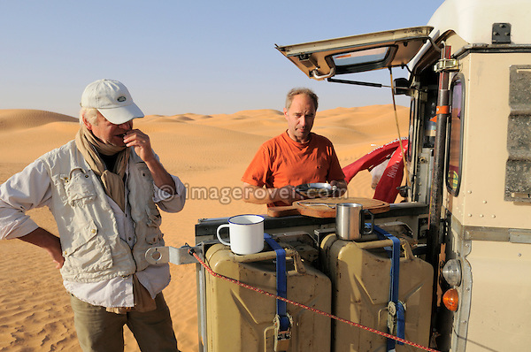 Africa, Tunisia, nr. Ksar Rhilane. Desert travellers Gernot and Siegried having a small breakfast at the rear of their Series 3 Land Rover 109 Dormobile. --- No releases available, but releases may not be needed for certain uses. Automotive trademarks are the property of the trademark holder, authorization may be needed for some uses.  --- Info: Image belongs to a series of photographs taken on a journey to southern Tunisia in North Africa in October 2010. The trip was undertaken by 10 people driving 5 historic Series Land Rover vehicles from the 1960's and 1970's. Most of the journey's time was spent in the Sahara desert, especially in the area around Douz, Tembaine, Ksar Ghilane on the eastern edge of the Grand Erg Oriental.