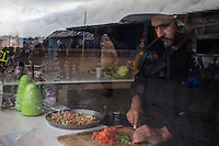 FRANCE, Calais: 18 December 2015 A refugee prepares fresh fruit and vegetables in his 'restaurant' as police patrol through in the reflection in the refugee camp known as 'The Jungle'. The camp in Calais is now believed to hold 7,000 refugees, who are all trying to prepare for the cold winter months ahead.<br /> Rick Findler / Story Picture Agency