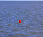 AYBRD2 Red buoy in sea with large ship off on the horizon