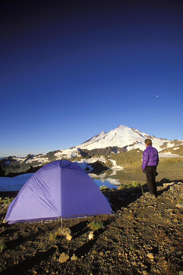 Backpacker beside tent below Mt Baker on a clear morning, North Cascades, Cascade Mountains, Washington