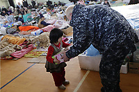 Navy Adm. Robert F. Willard, commander of U.S. Pacific Command, gives a toy to a child while touring a shelter facility in Ishinomaki city, Miyagi Prefecture, Japan, March 23. Willard and John V. Roos, U.S. ambassador to Japan, assisted in the delivery of relief supplies to displaced citizens. Since March 12, Marines and sailors have delivered food, fuel, water and supplies to disaster-stricken areas near Sendai as part of Operation Tomodachi. (Photo by: Lance Cpl. Steve Acuff)