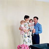Portrait of Michael and Andrea Gordon standing in their living room holding their twin daughters