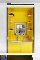 A white kitchen cupboard with doors that fold back, which conceal a sink in a vibrant yellow recess with a little window.