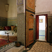 The walls of the bedroom suite are lined with decorative tiles and carved wooden doors lead through to an intimate sitting area.
