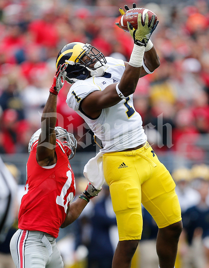 Michigan Wolverines wide receiver Devin Funchess (1) catches a pass under pressure from Ohio State Buckeyes cornerback Doran Grant (12) in the first quarter the college football game between the Ohio State Buckeyes and the Michigan Wolverines at Ohio Stadium in Columbus, Saturday morning, November 29, 2014. As of half time the Ohio State Buckeyes and Michigan Wolverines were tied 14 - 14. (The Columbus Dispatch / Eamon Queeney)