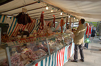 Stall holder and customer at the french food market in the Bastille area of Paris, France.