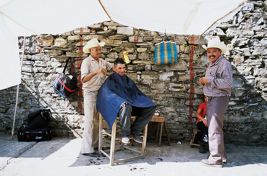 A mans has his hair cut on the street in Xilitla, a small village in the Sierra Gorda of Mexico where surrealist artist and British blue blood Edward James chose to settle and construct his surrealist sculptures in its jungles.