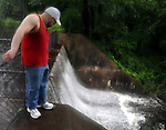 Fred Pirtel, of Manchester, looks down at the raging water fall at Globe Hollow in Manchester,  Sunday, August 28, 2011, during Hurricane Irene that caused widespread damage in Connecticut and a long the East Coast. (Jim Michaud/Journal Inquirer).