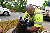 NWA Democrat-Gazette/J.T. WAMPLER Greg Battles of Rogers works Thursday April 20, 2017 at installing a pedestrian crossing signal at the Central Ave. intersection with the Razorback Greenway Trail in downtown Bentonville. Battles works for All Electric Service.