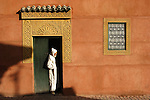 A man stand in front the entrance of a local house, Marrakech, Morocco