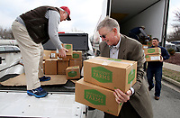 NWA Democrat-Gazette/DAVID GOTTSCHALK Pete Jenkins (from left), a volunteer at the Fayetteville Senior Activity and Wellness Center, Jerry Mitchell, executive director with the Area Agency on Aging of Northwest Arkansas, and Derek Burleson, public relation manager with Tyson Foods, load donated protein Thursday, March 1, 2018 in front of the Springdale Senior Activity and Wellness Center. Tyson Foods donated 8,000 pounds of protein and 11,500 Pack Shack meals, to Meals on Wheels of Washington County. Meals on Wheels of Washington County delivers approximately 16,000 meals a month. Meals on Wheels of Washington County delivers approximately 16,000 meals a month. Tyson Foods team members recently volunteered to assemble the donated Pack Shack meals.