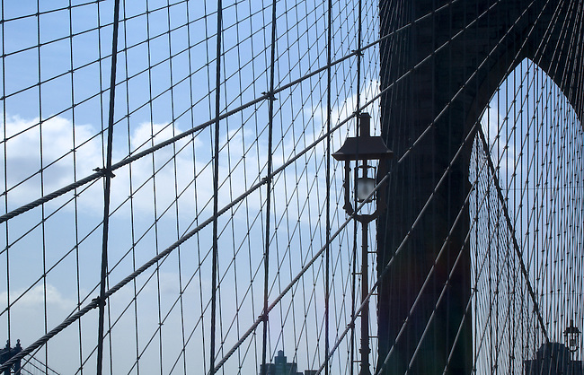 Close up image showing the geometric patterns created by the Brooklyn Bridge's support wires against a blue clouded sky. Wires sweep from the lower left edge of the image up to the upper right corner looking silver against the black background of one of the bridge's arches.