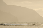 A paddleboarder heads out to see at Ke'e Beach on the Na Pali Coast, Kauai, Hawaii