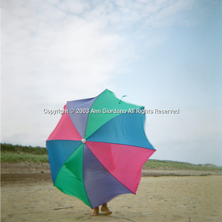 Man carrying colorful beach umbrella in wind with only feet showing