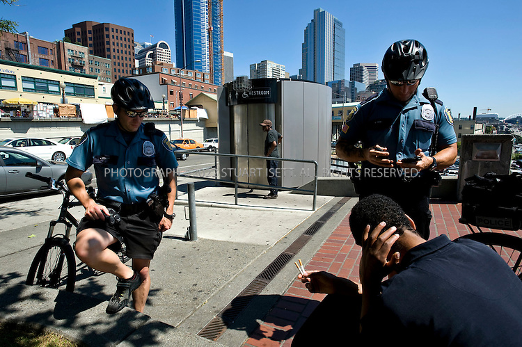 7/9/2008--Seattle, WA, USA.Police talk with a homeless man in Seattle's Steinbrueck Park. Behind is one of five automatically cleaning toilets that was installed in Seattle's Steinbrueck Park near the famous Pike Place Market. The five toilets cost taxpayers about $4.3 million but will soon be closed. The automated city toilet at the Steinbrueck Park is notorious for prostitution and drug activity..Steinbrueck Park has been part of Seattle's most crime-ridden census tract since 1985; on June 28th, 2008, 4 people were shot and injured in the park which sits next to Seattle's Pike Place Market, the city's most popular tourist attraction. .©2008 Stuart Isett. All rights reserved.
