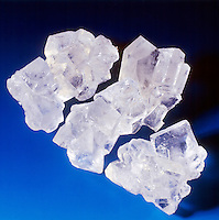 ROCK CANDY: RECRYSTALLIZATION OF SUGAR<br /> Sugar in Crystalline Form<br /> When molecules of a liquid are cooled slowly they arrange themselves in an orderly way. The sugar in rock candy has solidified slowly to a crystalline form. Quickly cooled molecules freeze into a disordered state of the liquid, i.e. glass.