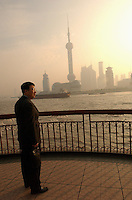 A man in a park looking at the skyline of the financial district of Pudong in Shanghai, China..