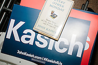 "A copy of ""Every Other Monday"" lays on top of campaign signs after Republican presidential candidate and Ohio governor John Kasich spoke at a town hall campaign event at the Derry VFW in Derry, New Hampshire."
