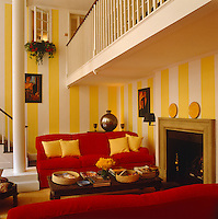 A cluttered coffee table is placed between two large red sofas in this yellow and white striped living area